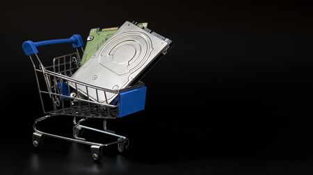 Two laptop hard drives in a blue shopping basket. Black background. Sale and discount concept, black friday, cyber monday. Copy space. Template for the design of an advertising banner. Installments for the purchase of computer peripherals and accessories. Imagens