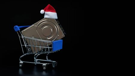 Santa Claus hat on a hard drive in a shopping cart. The concept of seasonal New Year and Christmas discounts on electronics and computer accessories. Black friday, cyber monday. Template for the design of sales and bonuses. Imagens