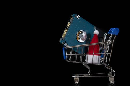HDD and Santa Claus hat in a shopping trolley. The concept of New Years gifts and Christmas discounts on computer accessories. Black friday, cyber monday. Template for the design of sales and bonuses. Copy space. Imagens