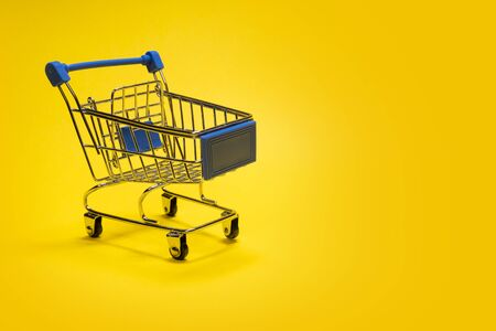 Gift stroller for shopping. Template for advertising purchases online or offline. Concept for discounts and sale, business and shopping cart of a buyer or seller. Yellow background. Copy space. Imagens