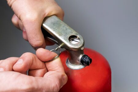 Male finger pulls out a pin. A man pulls out a safety ring from a red fire extinguisher. Fire fighting regulations. Close-up. Emergency Prevention. Shallow depth of field. Selective focus.