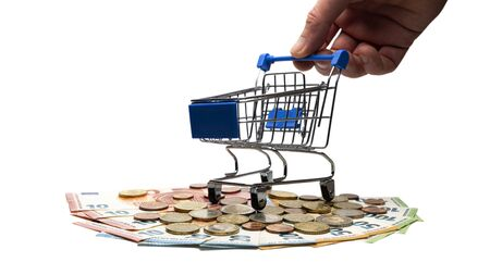 The male hand holds a shopping trolley, which stands on banknotes and euro coins. Close-up. Isolated. The concept of the consumer basket in European countries, crisis or wealth, sale or accumulation. Imagens