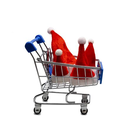 Four Santa Claus hats in a shopping trolley. The concept of a family consumer basket or Christmas shopping, seasonal Christmas sale. Advertising object. Close-up. Isolated.