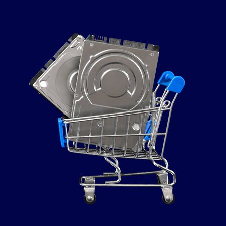 Two computer hard drives for the price of one in a shopping cart. Promotion and sale of peripherals and accessories for PC and laptop. Concept for cyber monday advertisement. Close-up. Isolated on a blue background.