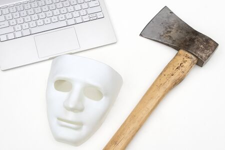 Mask, computer and ax on a white background. Close-up. Conflict criminal concept of cyber attack or defense against hackers. Imagens