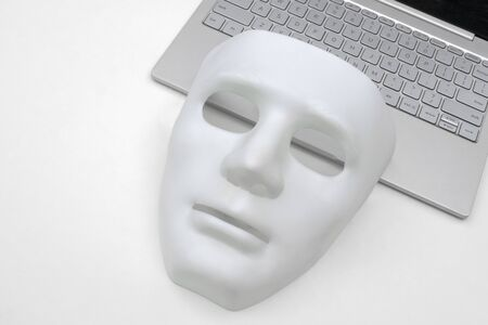 White mask and laptop closeup. The criminal concept of cyber attack or danger from hackers.