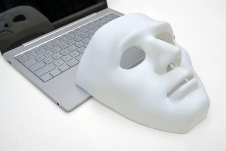 Mask, laptop on a white background. Close-up.Concept of cyber attack or defense against hackers.