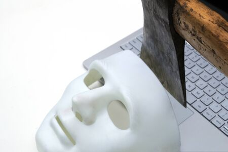 The ax symbolically cuts off the mask of an anonymous hacker from the laptop keyboard. We know how to protect data on your computer - advertising anti-phishing programs. The concept of cyber hacking and protection against online attacks. Close-up.