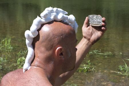A bald guy with a shaving foam mohawk looks in the mirror. Ecotourism or traveler lifestyle. A man shaves in nature near a river with green grass.