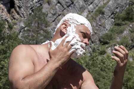 A man puts shaving foam on his bald head and face. The guy holds his hand on his cheek and looks in the mirror. Eco tourist in the mountains or traveler lifestyle. Hygiene and beauty concept during tourism. Stockfoto - 134038131