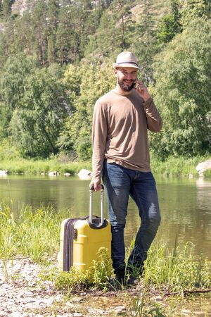 A guy in a hat and jeans is talking on the phone outdoors. A concept of leisure and travel. Hipster young man hitchhiking along a mountain river with a yellow suitcase.