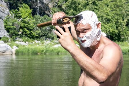 A brutal Caucasian guy shaves his bald head with a sharp ax at himself in the mirror. The head and face of a man are covered with soap foam. Traveler lifestyle in the mountains. The concept of hygiene in nature.