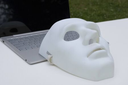 White mask and laptop closeup. Remote hacking data. The concept of hackers in nature. Imagens
