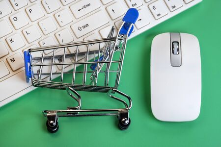 White keyboard and mouse for a computer on a green background. Shopping trolley lies on the keys. Concept online shopping, black friday and cyber monday, discount and sale of computer accessories. Wireless technology. Details close up.