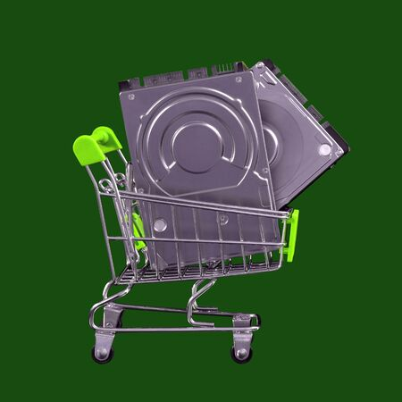 Buy two hard drives for the price of one. HDD in a shopping trolley. Isolated on a green background. The concept of recycling and environmental safety. Sale and discounts on accessories for a computer and laptop. Black friday and cyber monday.