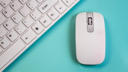 A wireless mouse lies next to a white computer keyboard. Close-up. Blue background. The concept of the office manager or computer salon selling peripheral devices.