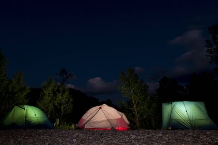 Three tents glowing from the inside on a night forest background. Dark blue sky, trees silhouettes, stone soil. The concept of travel, leisure and wild tourism. Copy space. Stockfoto