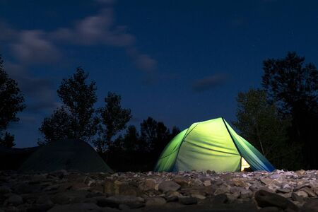 Dark and luminous tourist tents against the background of the evening forest and blue sky with clouds. Film noise, grain, high ISO. Night campground for tourists with stones on the ground. Copy space. The concept of travel, leisure and tourism. Stockfoto