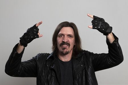 Portrait of an adult long-haired man in a black jacket and fingerless gloves. A guy who looks like a Mexican biker or heavy metal musician. Rock fan makes corna gesture.