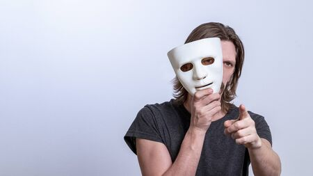 The concept is you next, fraud or a lie. A long-haired man in a gray T-shirt looks out from behind a white mask and points his finger at the camera. Copy space. Gender or split personality. Caution Warning.