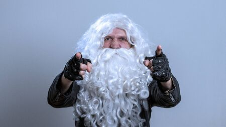 Santa Claus in a black biker jacket and gloves points his fingers forward. Evil emotion - concept: you are next. A long-haired man in a white wig and a beard as a rock fan or heavy metal musician and looks at the camera.