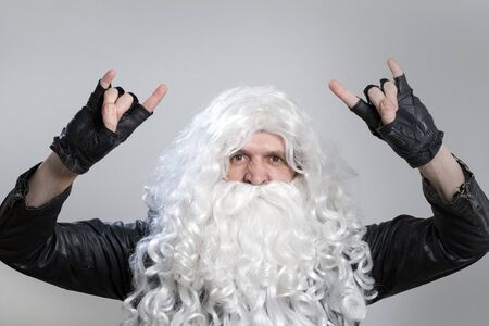 A tough guy in a wig and a beard like Santa Claus makes a heavy metal gesture. Man in a black biker jacket and gloves as rock fan or heavy metal musician looks at the camera. Stock Photo