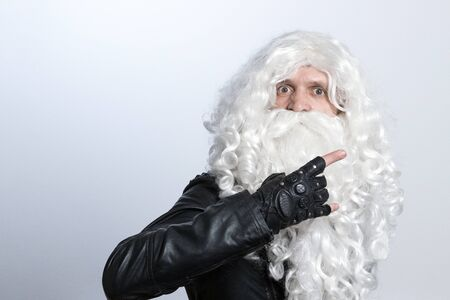A tough guy in a white wig and a beard like Santa Claus making an heavy-metal gesture and staring at camera. Copy spase. Music rock Christmas concept. Archivio Fotografico