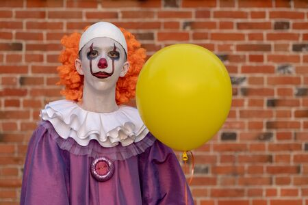 A guy in a clown costume with a yellow balloon against a brick wall. Costume for carnival, all saints day or halloween.