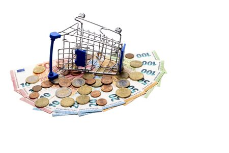 The stroller for shopping is tipped over on a fan of Euro banknotes and coins. The concept of a consumer basket and spending money in Europe, crisis, discounts, interest return. Banknotes in the amount of 500 euros. Template for black friday, cyber monday.