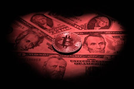 Bitcoin inside a heart-shaped light red spot on a background of dollar bills. Cryptocurrency discount concept for valentines day, wedding electronic sales. Dark background.