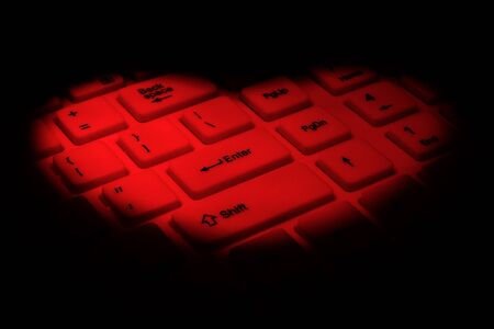 Bright red spot in the shape of a red heart on a computer keyboard. The concept of congratulations on Valentine's Day, love through the Internet, dating and flirting on social networks. Black background.
