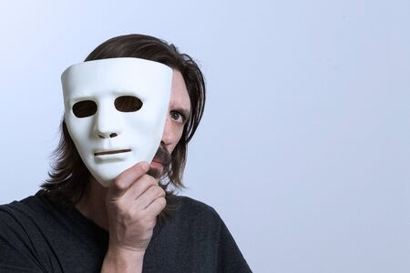 A long-haired man with a mustache holds a white mask near his face and looks out with one eye. The concept of concealment of identity, peeping, hacking data. Caution scammers. Copy space.