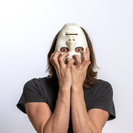 A long-haired man in a gray T-shirt covers his face with a white mask upside down and tries to tear it off himself. The concept of personality crisis, fear, paranoia or mental disorders. Inverted world, eyes in horror, loss of self-control.