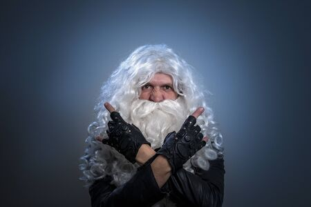 A tough guy in a wig and a beard like Santa Claus makes a heavy metal gesture with his arms folded across his chest and looks at the camera. Christmas rock concept. Long-haired man in a black jacket and fingerless gloves. A guy who looks like a biker or heavy metal musician.