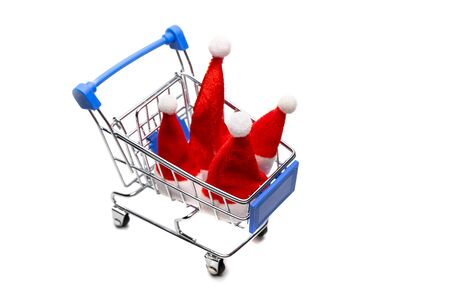 Four santa claus caps in a souvenir shopping trolley. New Year concept for design family Christmas shopping, discounts and sales. Isolated object on white.