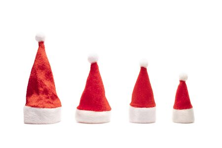 Set of red Santa Claus hats. Family New Year and Christmas holidays. Four souvenir isolated caps with raised bells. Copy space on white background.