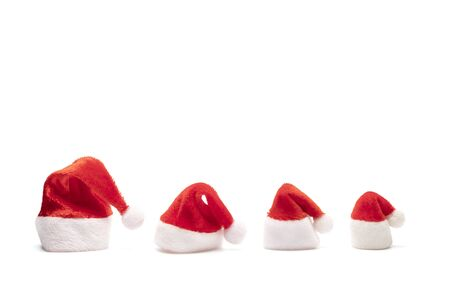 Set of red Santa Claus hats on white background. Four souvenir isolated caps with bells lowered. Copy space. Family New Year and Christmas holidays. Archivio Fotografico