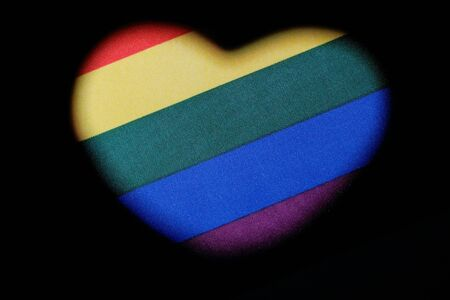 Heart shape on the LGBT rainbow flag. Symbol of love and freedom. The concept of tolerance and independence of sexual minorities is the celebration of homosexual Valentine's Day. Black background. Archivio Fotografico