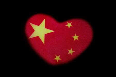 Heart shape on a red flag with yellow stars. Symbol of love and Chinese patriotism. Black background. The concept of a wedding in China or a celebration of Valentine's Day. Archivio Fotografico