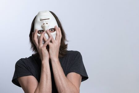 A man with long hair holds an inverted mask on his face. The dynamic inclination of the male body characterizing the problems of the psychophysical state of a person or mental disorder. Strange psychedelic concept.