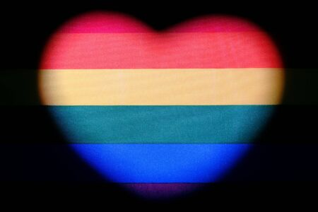 Heart shape on the rainbow flag. Symbol of LGBT love and freedom. The concept of tolerance and independence of sexual minorities is the celebration of homosexual Valentines Day. Black background.