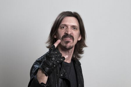 Crazy young man in black leather jacket doing rock gesture over gray background. A guy with long hair holds a fingerless glove in front of him. Concept of biker community, rock fan. Archivio Fotografico