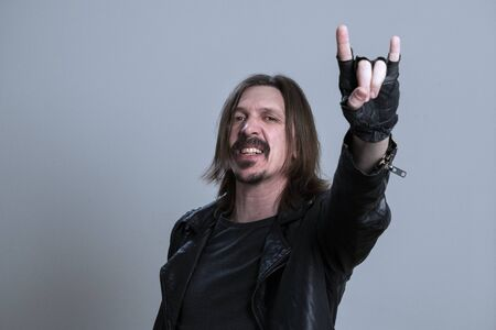 hand. Concept of biker community, rock fan. Crazy young man in black leather jacket doing rock gesture over gray background. A guy with long hair raised his fingerless gloved hand. Concept of biker community, rock fan.