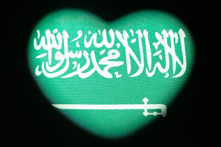 Heart shape on the flag of Saudi Arabia. For design and illustration of the relationship and feelings of the newlyweds. The concept of love for the motherland, patriotism and independence. Valentine's Day. Dark background. Copy space. Archivio Fotografico