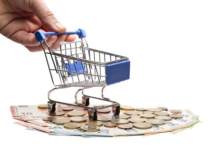 The concept of the consumer basket in European countries, crisis or wealth, sale or accumulation. Isolated. The male hand holds a shopping trolley, which stands on banknotes and euro coins. Close-up.