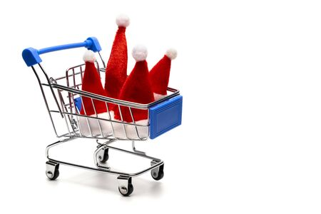 Family Christmas purchases or New Year discounts at the supermarket or online store. Four Santa Claus hats in a shopping trolley. Isolated. Object for advertising. Consumer basket of winter holidays.