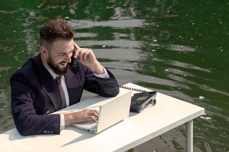 Businessman in the swamp. A young bearded man in a suit sits at an office desk with a white laptop and speaks while smiling on the phone. Green water sucks manager or tech support concept. Routine of an employee.