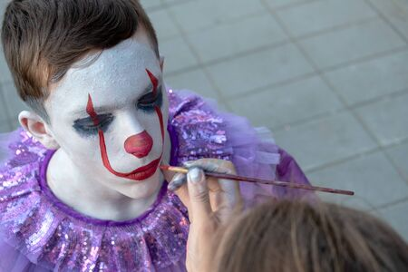 Street makeup. Cosplay at a horror party. Artist's hand with a brush paints the face of a teenager guy. The image of a clown or mime. Costume for carnival or holiday halloween.