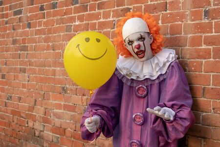 Scary clown with a cheerful yellow ball. The guy near the old brick wall. Conflict and fear. Costume for carnival or holiday halloween. Cosplay at a horror party. Copy space.