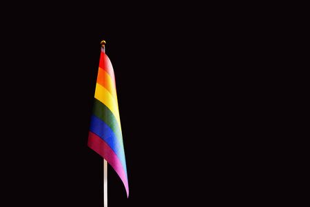 LGBT flag in rainbow colors. The concept of love, independence and freedom for gay people, homosexuals, lesbians and other sexual minorities. Copy space. Black background.